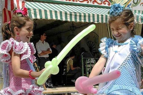 Niñas jugando con globos en la Feria de Abril. | Carlos Márquez
