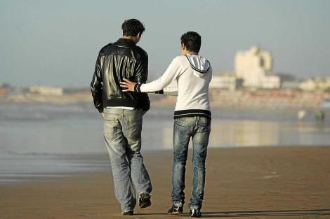 Dos jóvenes pasean por una playa en Marruecos.| E. Calvo