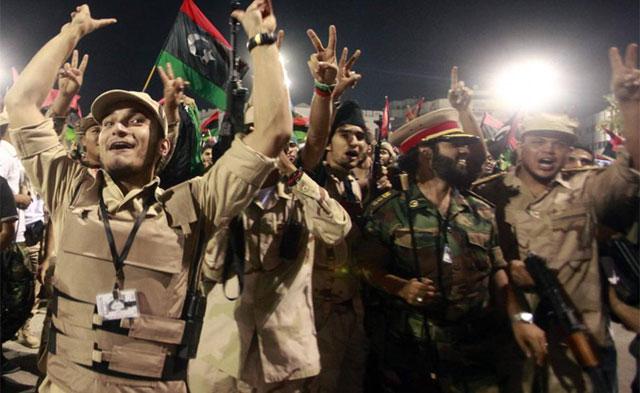 Soldados del Gobierno interino celebran en las calles de Trípoli la caída del dictador Gadafi. | Reuters
