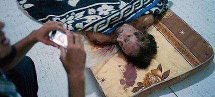 Un hombre fotografía el cadáver de Gadafi en Misrata.   AP