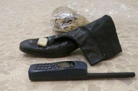 El teléfono 'Thuraya', la bota de cuero negro, el turbante y el amuleto los tenía Gadafi consigo, junto a un revolver, cuando fue detenido. Están ahora en un museo en Sirtre. | Efe