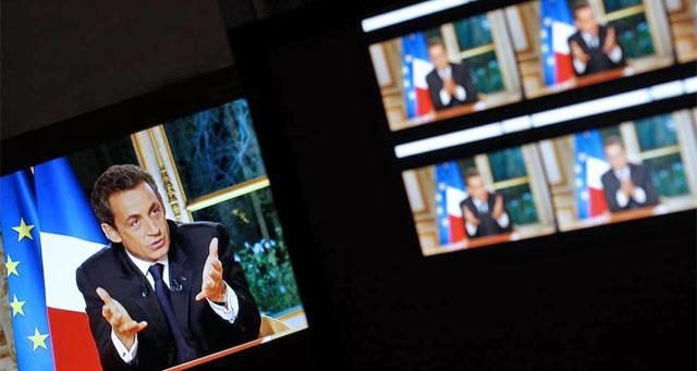 Las pantallas de televisión muestran la entrevista al presidente francés. | Afp
