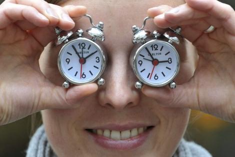 Una empleada del fabricante de relojes Carlton, en Munich, bromea con dos despertadores. | Efe