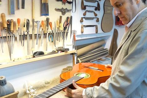 Felipe Conde, dueño del taller, mostrando el proceso de fabricación de una guitarra.