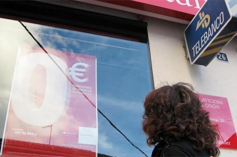 Una mujer consulta el cartel de una promoción bancaria en el escaparate de una sucursal. | EM