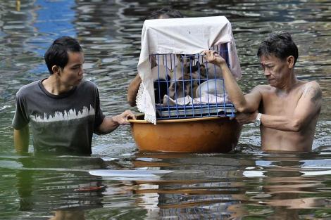 Dos hombres, en una de las muchas calles inundadas de Bangkok. | Efe