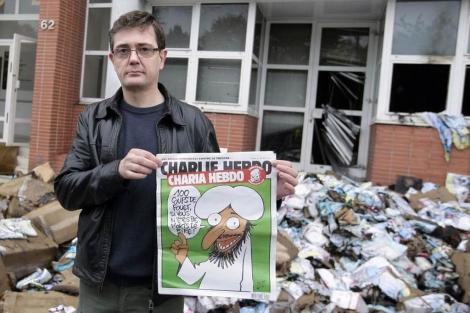 El editor del semanario muestra el último número en la sede destrozada. | Afp