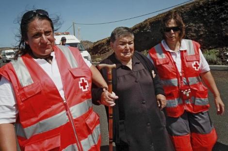 Miembros de la Cruz Roja ayudan a evacuar La Restinga.   EL MUNDO