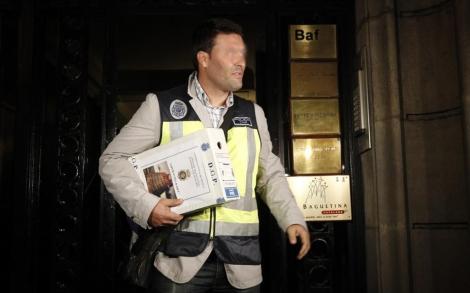 Un agente sale con documentos de la sede de la empresa. | Quique García