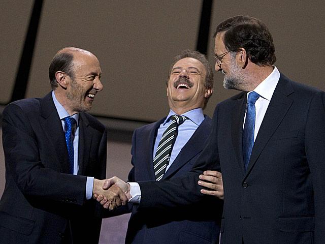 Rubalcaba y Rajoy se saludan el inicio del debate junto al moderador, Campo Vidal. | AP/Arturo Rodríguez