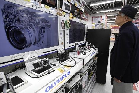 Un hombre mira productos de Olympus en una tienda de Tokio. | Reuters