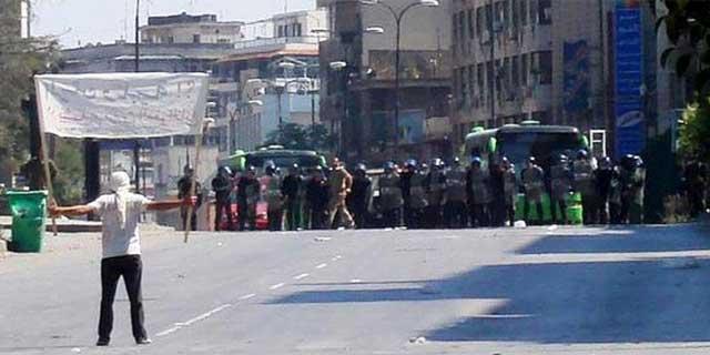 Un manifestante frente a un cordón de policías antidisturbios en Jalidia, cerca de Homs. | REUTERS