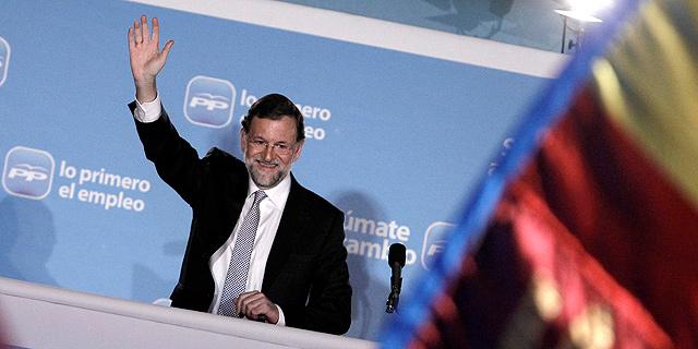 Rajoy saluda desde el balcón de la sede del PP. | Alberto di Lolli