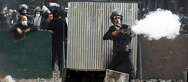 Un policía antidisturbios dispara gas lacrimógeno contra los manifestantes junto a la Plaza Tahrir, en El Cairo. | Reuters