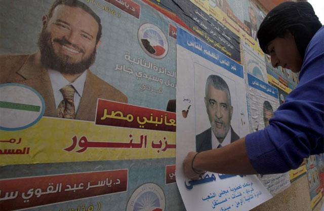 Pegada de carteles electorales en una calle de Alejandría. | Reuters