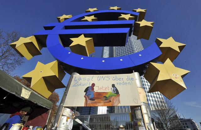 Exterior de la sede del BCE en Francfort, con un campamento de 'indignados' bajo el símbolo del euro. | Efe
