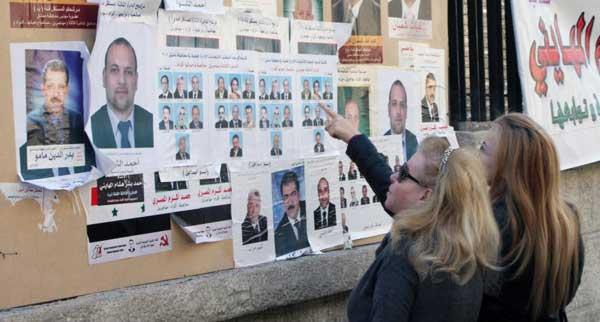 Dos mujeres miran los carteles electorales en una calle de Damasco. | AP