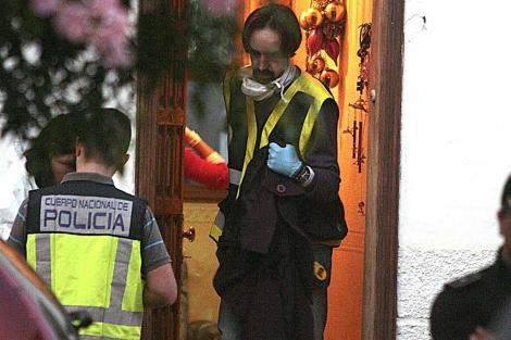 Un agente sale de la vivienda en la que fueron hallados los cadáveres de los niños. | Efe