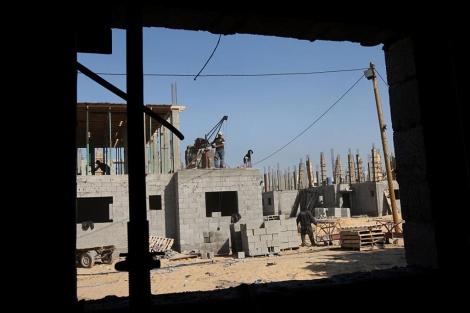 Trabajadores palestinos construyen casas en un proyecto de la ONU en Rafah. | Afp