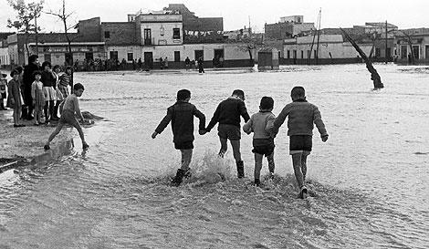Niños juegan en 1961 tras el desbordamiento del Tamarguillo.