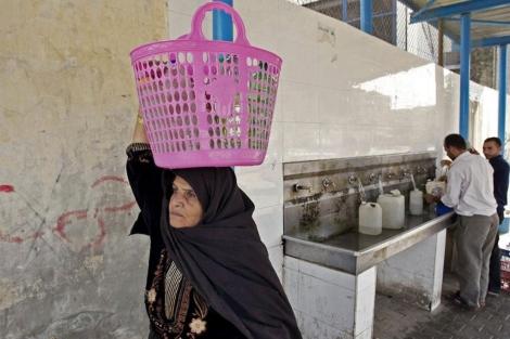 Una mujer palestina transporta botellas de agua en Khan Younis (Gaza).