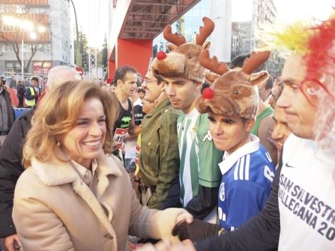 Ana Botella saluda a un grupo de participantes en la San Silvestre