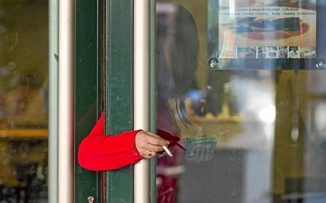 Una mujer fuma en la pueta de una cafetería de Madrid. | Gonzalo Arroyo