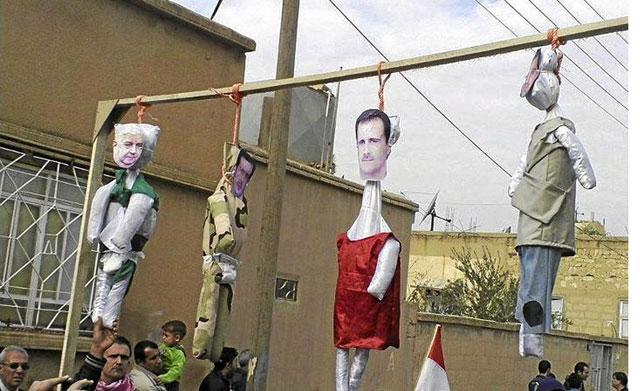 Muñecos de Bashar Asad y sus colaboradores colgados durante una manifestación en Amude.   Reuters