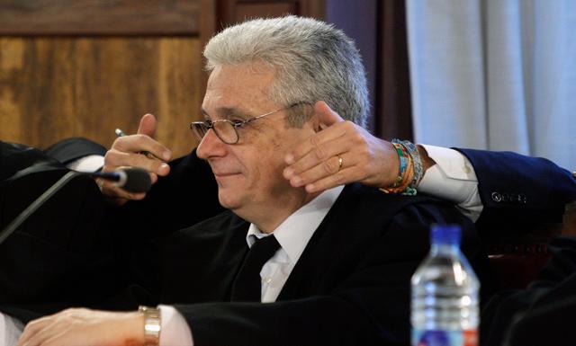 El abogado de Campse atiende al ex presidente, oculto tras él, durante el juicio. | Efe