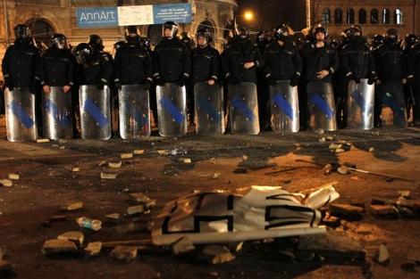 Policías antimotines vigilan una zona tras una pelea con manifestantes en Bucarest. | Efe