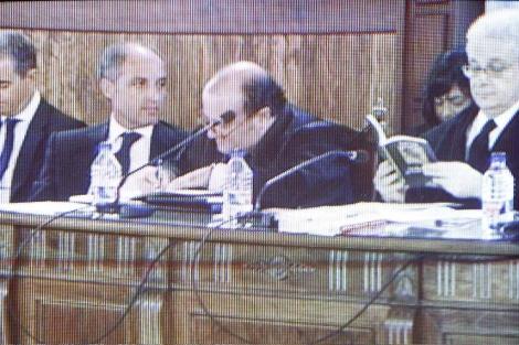 El abogado de Camps hojea el libro que ha llevado el ex presidente. | J. Cuéllar