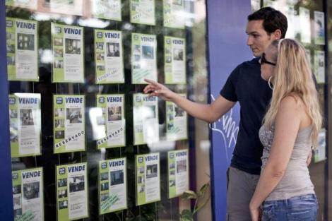 Una pareja mira anuncios en el escaparate de una inmobiliaria. | Roberto Cárdenas