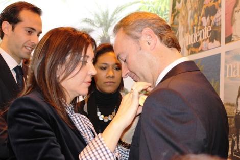 La alcaldesa de Elche pone una pequeña palma en la solapa del Presidente Fabra. | E.M.