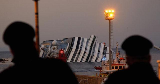 Dos carabinieri observan el Concordia desde el puerto de Giglio.   Reuters