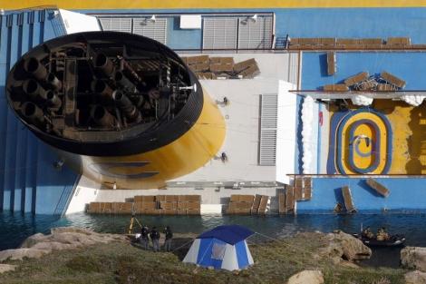 Tres hombres ante el 'Costa Concordia' en la isla italiana de Giglio. | Reuters