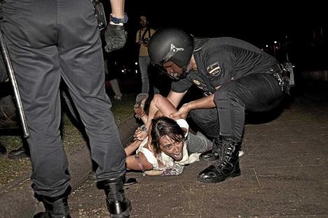 La policía detiene a una 'indignada' frente al Ministerio del Interior, en Madrid. | Luca Piergiovanni