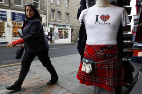 Una mujer camina cerca de una tienda de recuerdos en Edimburgo.   Reuters