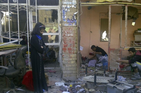 Una joven frente a un edificio destrozado tras el ataque en Zaafaraniya (Bagdad). | Reuters