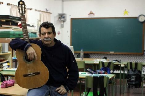 El profesor Miguel López Castro con su guitarra en un aula. | C. Díaz
