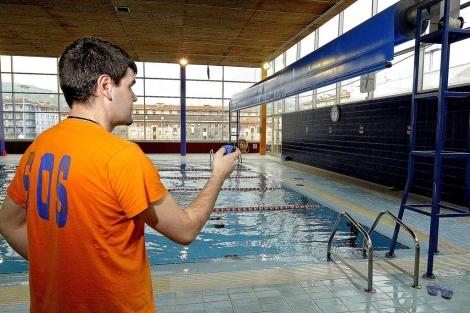 Un socorrista activa la lona que evita la vaporización del agua. | Patxi Corral