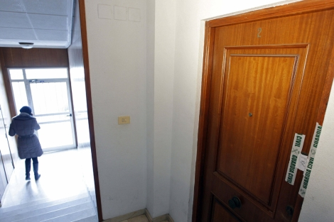 Puerta de la vivienda donde ha muerto una mujer presuntamente a manos de su pareja.   Efe