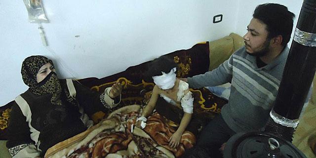 Una niña herida, junto a sus padres, en su casa de Bab Amro (Homs). | Reuters