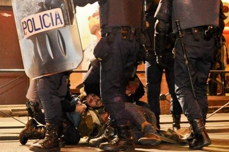Un manifestantes es inmovilizado por varios agentes de policía. | Gonzalo Arroyo