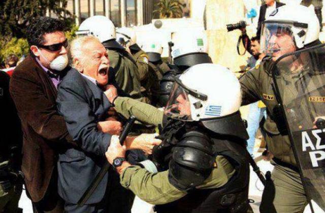 Manolis Glezos es zarandeado durante las protestas. | newsbomb.gr