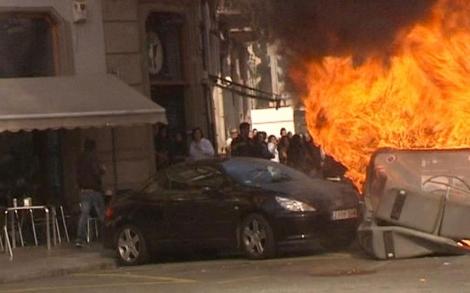 Un contenedor arde junto a un vehículo que también acabó en llamas.   Efe