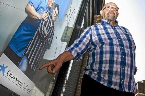 José Moreno señala un cartel de La Caixa. | Foto: Gonzalo Arroyo