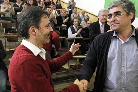 Xoán Bascuas y Carlos Aymerich se saludan al final de la asamblea.   Efe