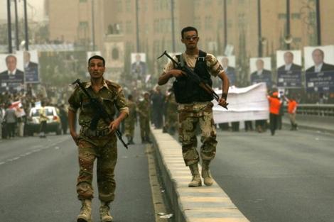 Dos miembros de las fuerzas de seguridad yemeníes patrullan las calles de Saná. | AFP