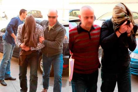 Los dos agentes (con la cara tapada) al ser trasladados.   Pep Vicens