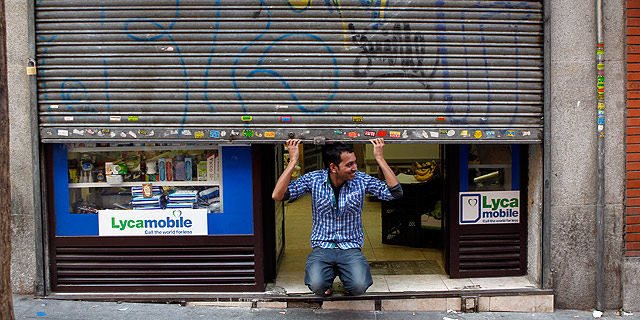 Un comerciante de Madrid sujeta la persiana metálica de su tienda. | Foto: Sergio González